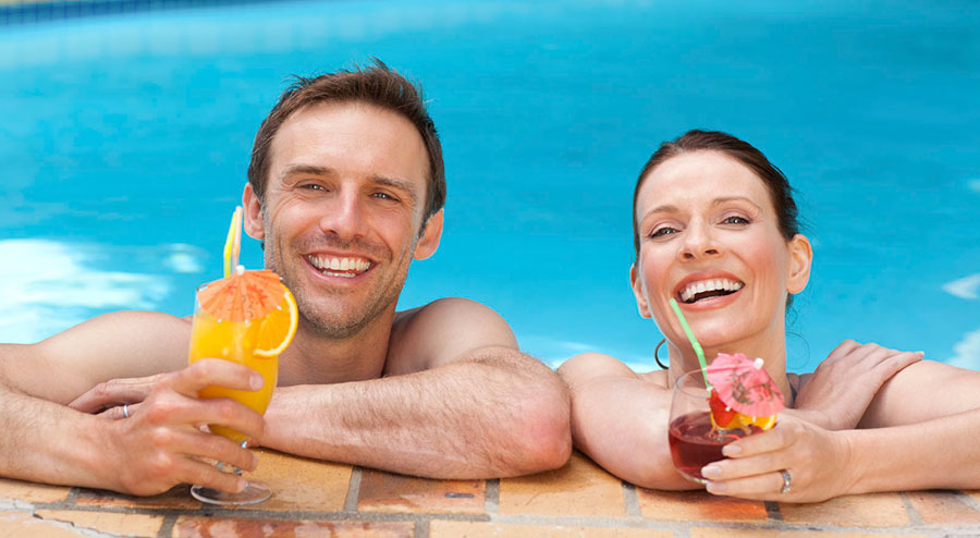 A couple having drinks on a pool
